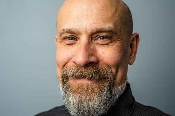 Homme chauve avec une barbe bien lissée