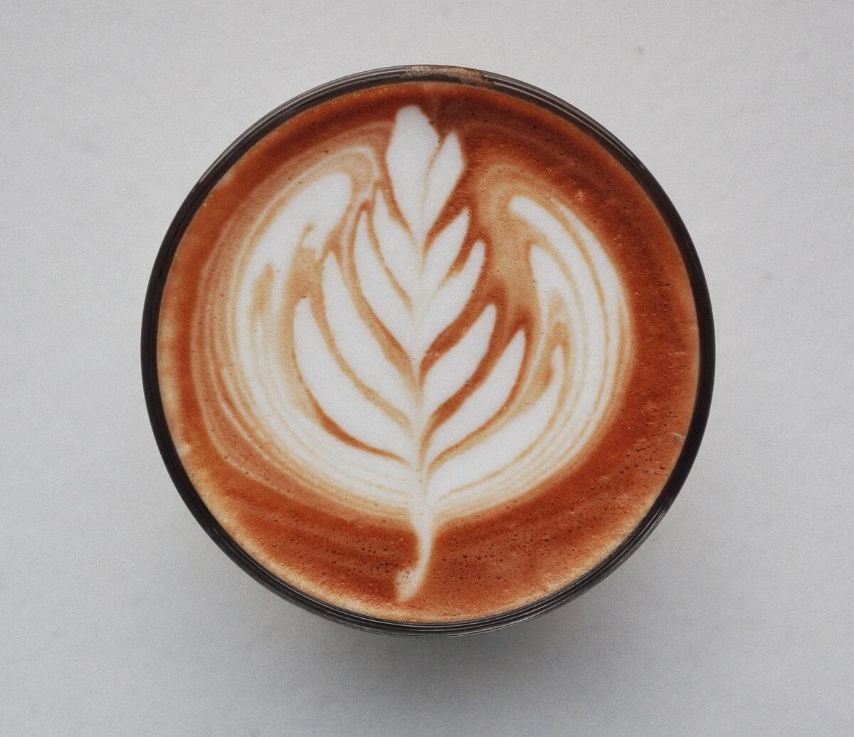 Café avec une mousse de lait en feuille