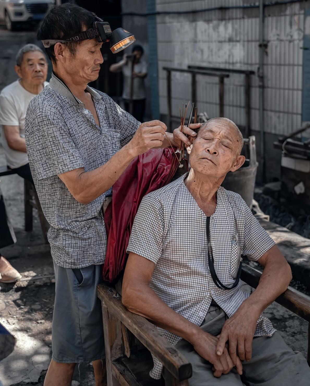 Homme en train de laver les oreilles d'un autre homme avec un oriculi