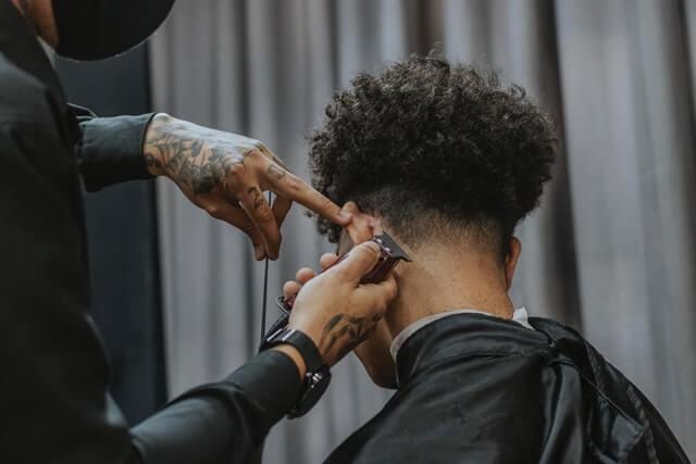 Dégradé américain : coiffeur qui travaille sur la nuque