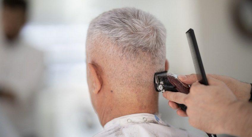 homme aux cheveux qui blancs en train de se faire couper les cheveux