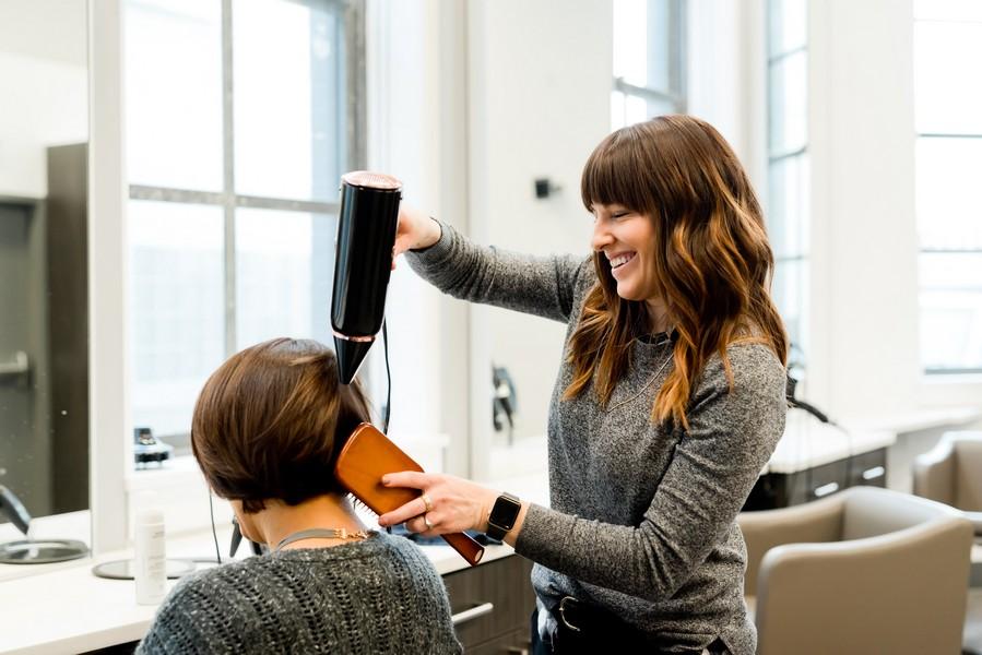 femme qui entretient sa coupe courte chez la coiffeuse