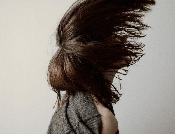 femme qui fait un mouvement avec ses cheveux
