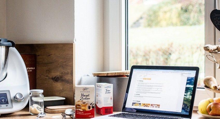 robot Thermomix et ordinateur posés sur le plan de travail d'une cuisine