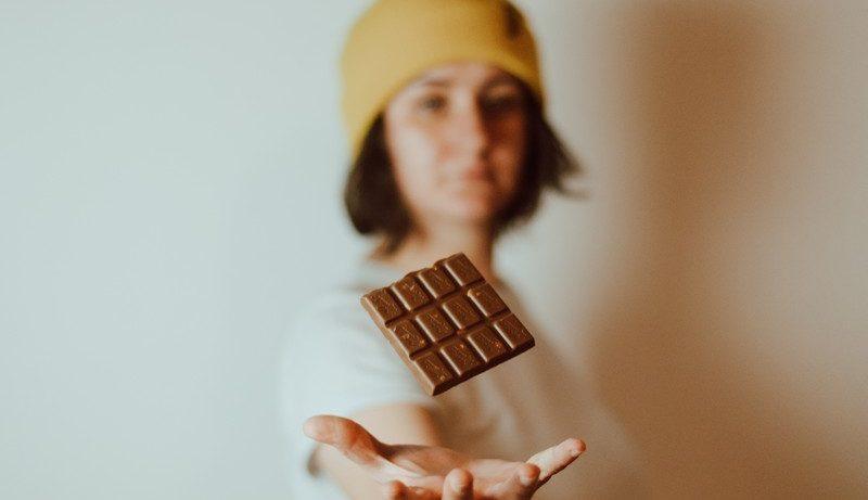 Femme qui lance une tablette de chocolat en l'air
