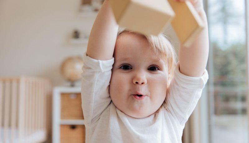 bébé qui tient un cube dans sa main