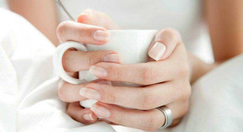 mains d'une femme qui tiennent une tasse blanche