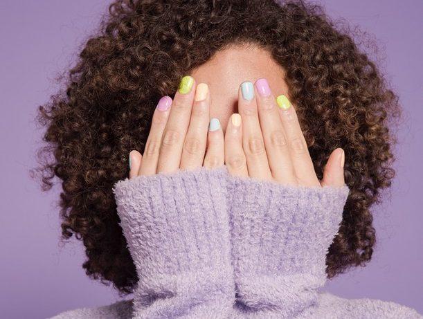 femme aux ongles multicolores qui cache son visage derrière ses mains