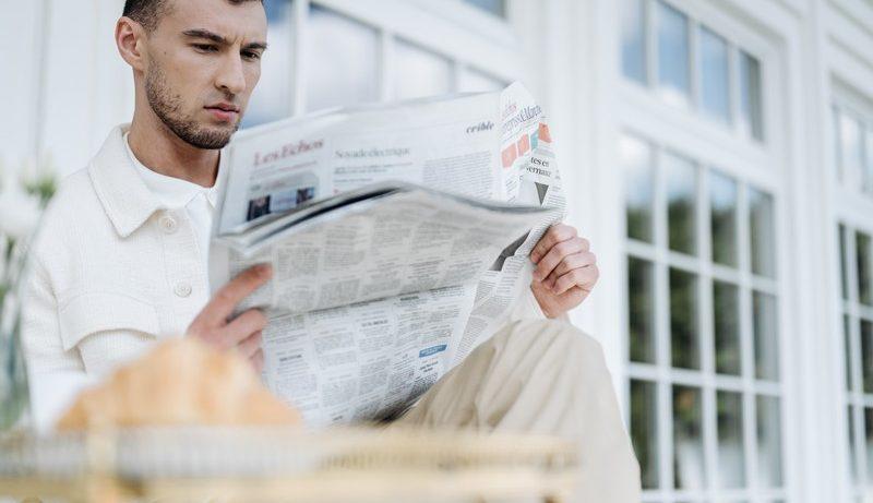 homme en chemise qui lit le journal