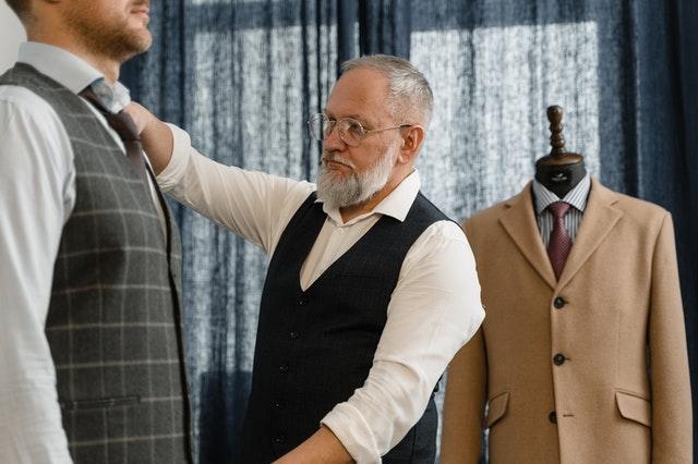 Couturier qui mesure un homme pour créer un habit sur-mesure
